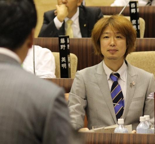 答弁に立つ吉田市長の後ろ姿と、質問者フジノ(本会議場にて)