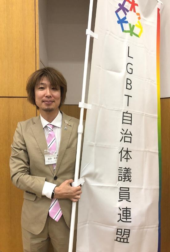 LGBT自治体議員連盟ののぼりを持つフジノ