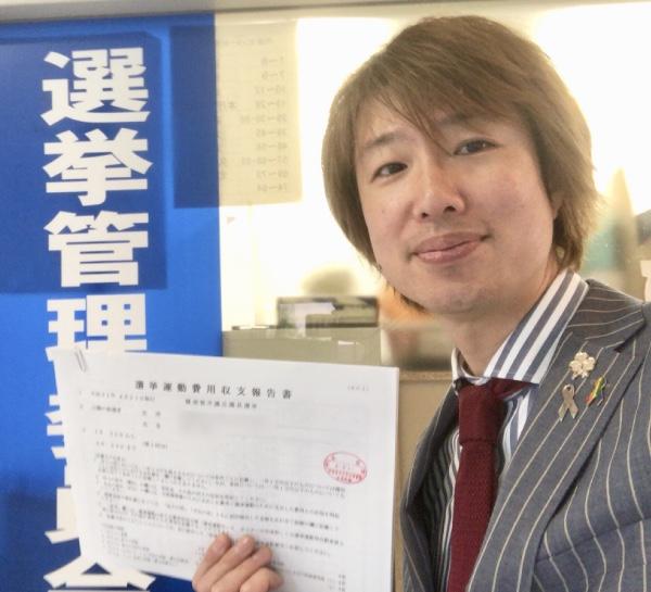 選挙管理委員会の受領印が押された「選挙活動費用収支報告書」を持つフジノ